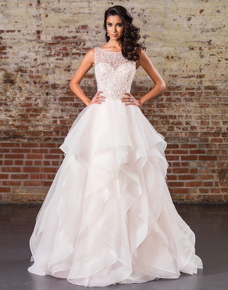 Justin Alexander signature wedding dresses style 9847 Look opulent in this ball gown with a Sabrina neckline, natural waistline, heavily adorned bodice, illusion V-back, and dreamy layered skirt with horsehair trim.