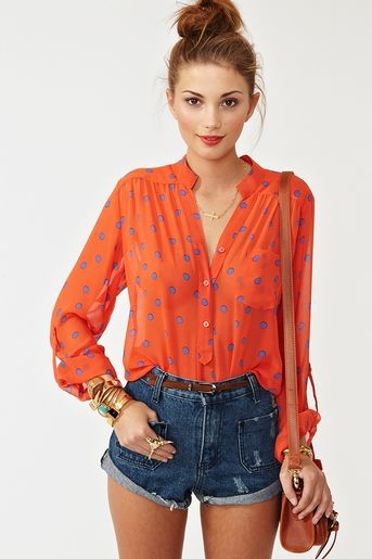 LOVE the flowy blouse tucked into high waisted jean shorts, topped with a messy top bun