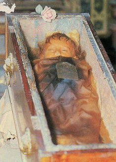"""Rosalia Lombardo was born in 1918 in Palermo, Sicily and died on December 6 1920. Rosalia's father approached Dr. Alfredo Salafia, a noted embalmer, to preserve her. She was one of the last to be admitted to the Capuchin catacombs of Palermo in Sicily. She appears as if she were only sleeping, hence receiving the name """"Sleeping Beauty"""" . She is kept in a small chapel at the end of the catacomb's tour and is encased in a glass covered coffin, placed on a marble pedestal."""