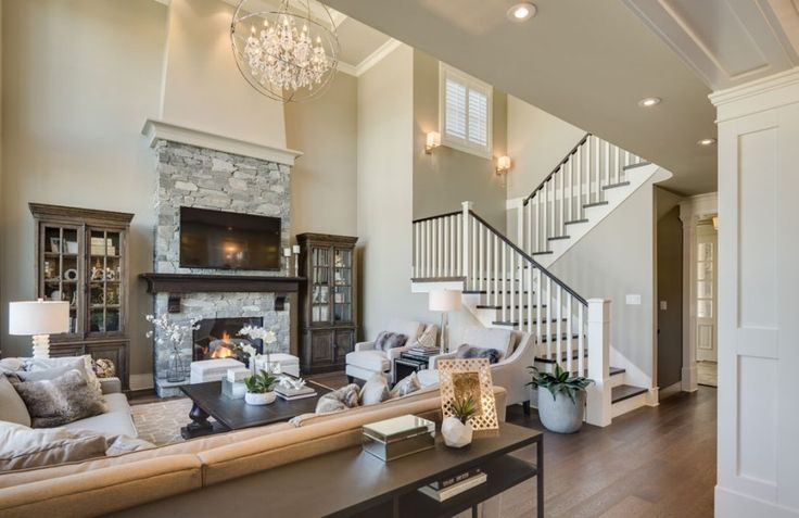 The short hall from the front door enters directly into the spacious living room with a large light gray stone fireplace. On either side of the fireplace is a matched pair of glass-faced curio cabinets. The large L-shaped sectional sofa and two armchairs provide ample seating.