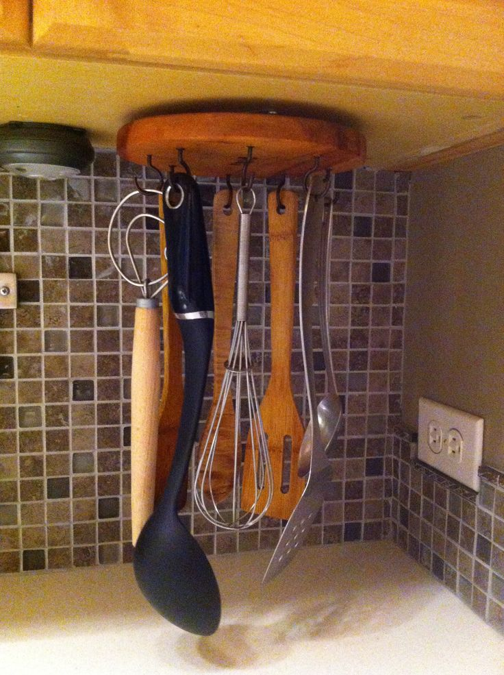 "unused ""lazy susan"", attach 8 cup hooks and installed under the kitchen cabinet. It is now a rotating utensil holder."