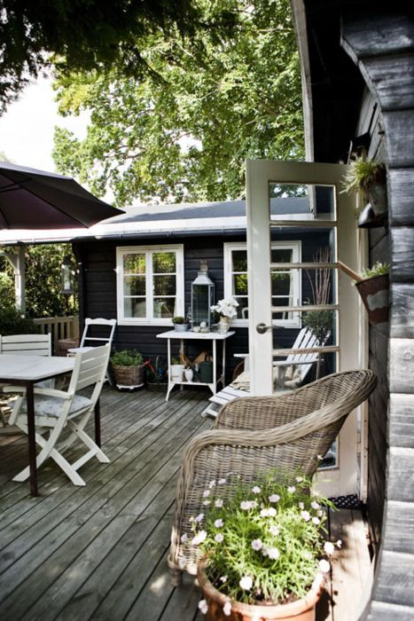 Black exterior, white trim, weathered deck and wicker.
