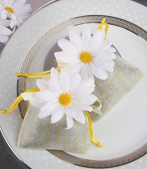 """Fresh As A Daisy"" Lavender Sachet Wedding Favor features a yellow and white gingham organza sachet that is filled with fragrant french lavender. The top of each sachet is hand tied with a yellow satin ribbon. The look is complete with a silk daisy. It has white petals and a yellow center."