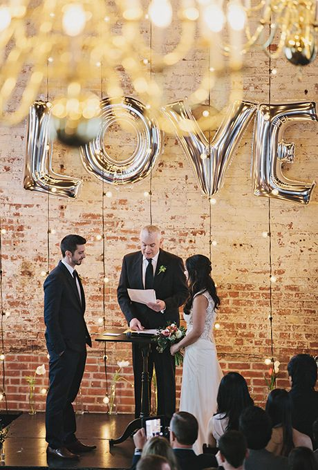 Brides.com: . An urban ceremony altar with metallic silver balloons and hanging string bulbs.