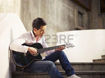 man%3A+jonge+man+zittend+op+stappen+gitaar+spelen+en+zingen