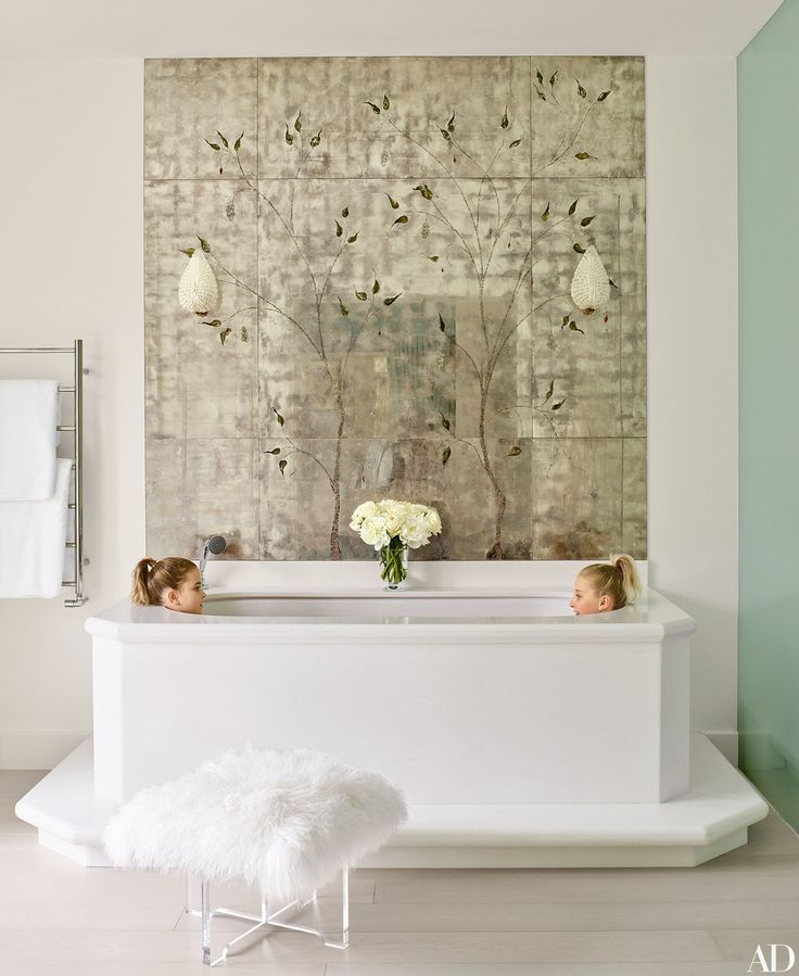 Painted mirror panels create an unexpected backdrop to a tub from C. P. Hart in the master bath of Nadja Swarovski's English country home.