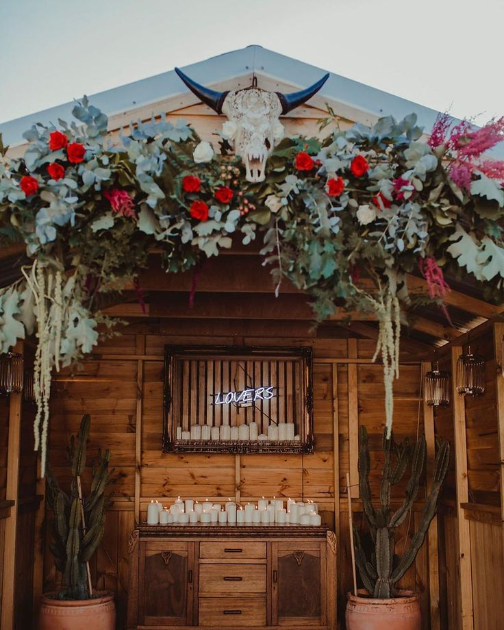 floral backdrop with bull skull for a bohemian backyard wedding
