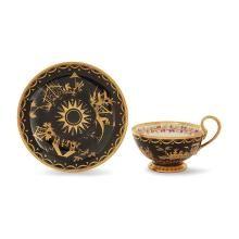 SÈVRES, 1804-1805Tasse à thé et sa soucoupe en porcelaine dure à fond noir à décor en or et platine de Chinois sur terrasses, pagode...