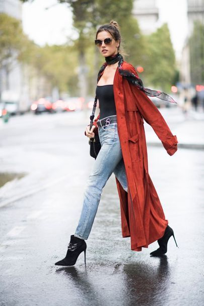 Allesandra Ambrosio wearing a light weight neck tied scarf with a long burnt red trench coat // Daily Style Directory -British Vogue