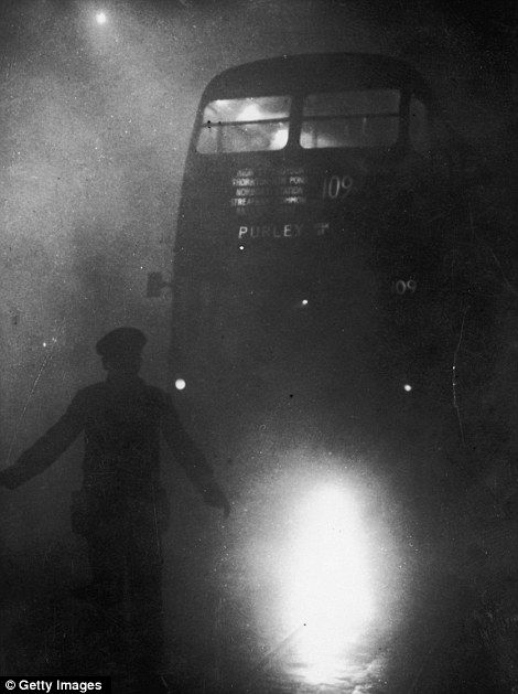 'A real pea souper': An official guiding a London bus through thick smog with a flaming torch in December 1952