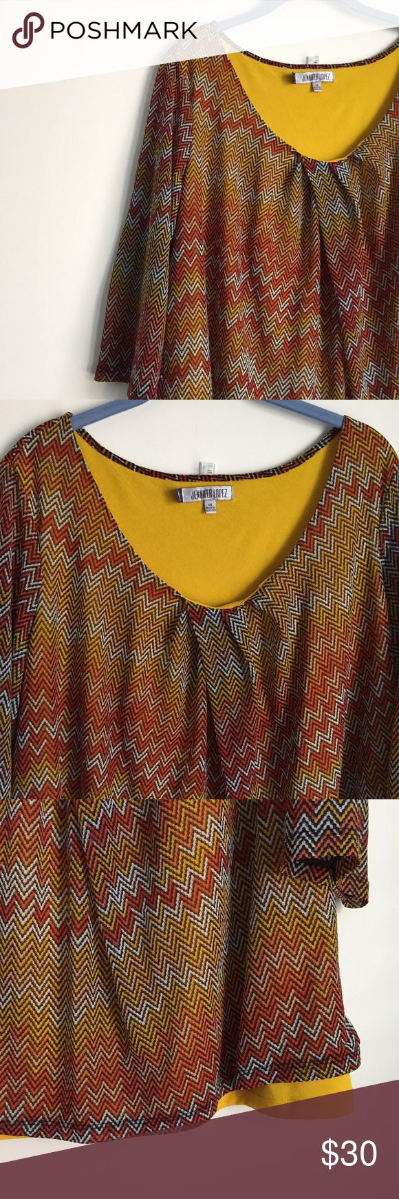 Jennifer Lopez Chevron Top 1X Vibrant chevron top with scoop neckline, mustard colored lining and 3/4 length sleeves.   Size: 1X 100% Polyester   Bundle & Save! 🛍 Jennifer Lopez Tops Blouses