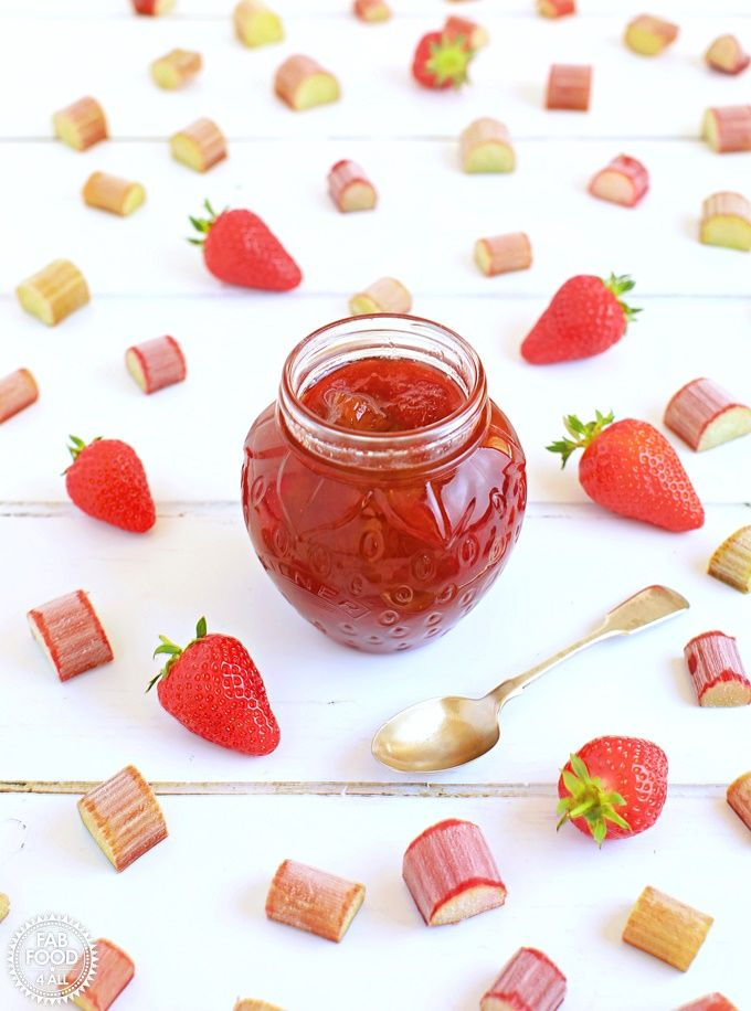 Pot of Rhubarb & Strawberry Jam with teaspoon surrounded by strawberries & slice…