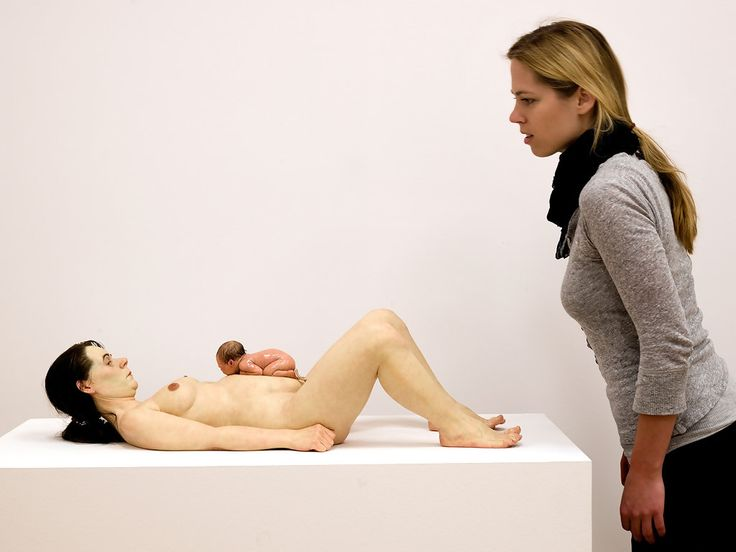 A young woman reacts to the sculpture 'Mother And Child' of artist Ron Mueck