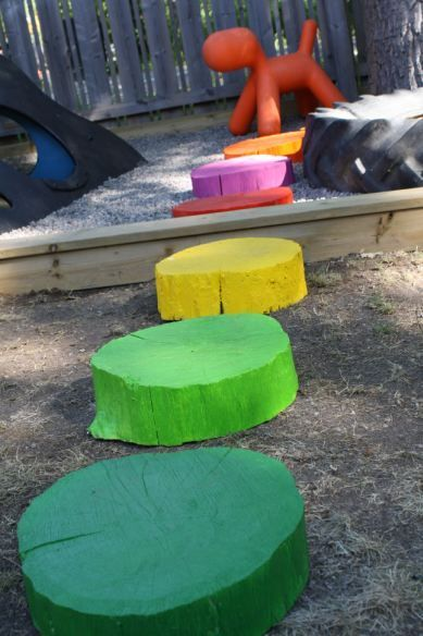 "tree trunk stepping ""stones"" painted bright colors"