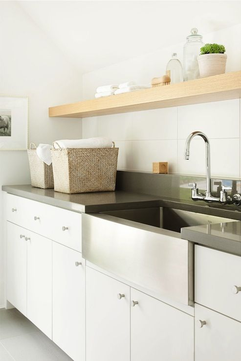 Sleek white laundry room cabinets pair with simple nickel hardware and glossy gray countertops.