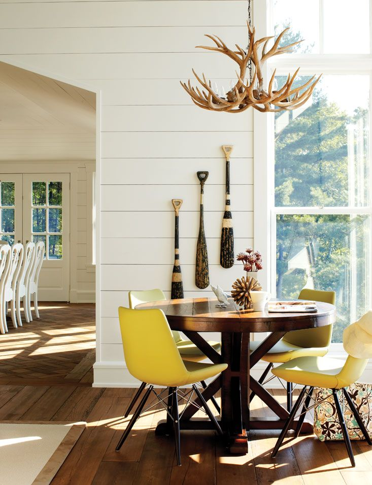white wood paneled walls, antler chandelier, paddles on walls. (Muskoka cottage decor - Chatelaine)