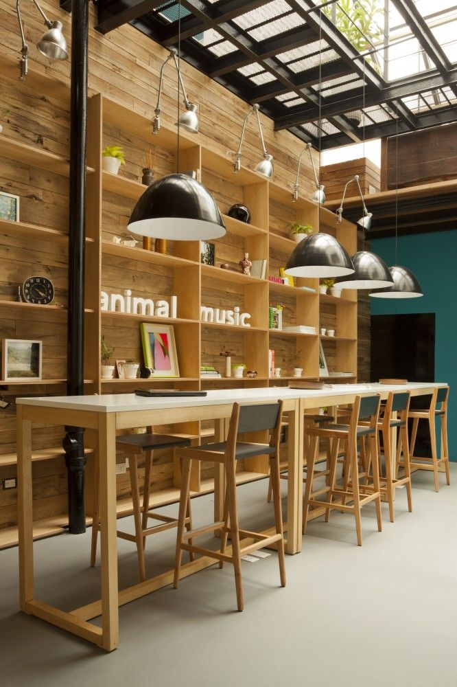 Animal Music Office | Wooden Office Interiors  Long, thin, bar height table as short term landing spot.  Could also stand here.