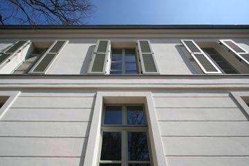 Holzfensterläden, Gesimse und Faschen erzeugen einen lebendigen Schattenwurf - Wohnhaus in klassisch traditionellem Baustil
