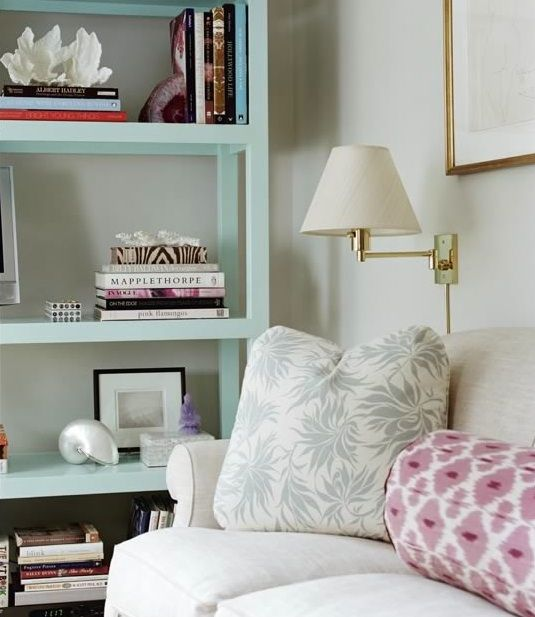 Ashley Whittaker. NYC apartment, Manhattan apartment, New York Apartment, NY apt. Ikat Madeline Weinrib bolster pillow, aqua colored painted bookcase.  Living Room.