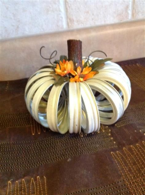 Are you getting ready to change up your decorating for the upcoming fall season? If yes, this pretty white pumpkin made from canning jar lids will be a lovely addition.<br/><br/>This pumpkin is made from 17 regular mouth rings, painted in white, and sealed. The stock is from a downed branch and has been sealed as well.<br/><br/>The silk leaves and the wire curly cues finish this cute pumpkin.<br/><br/>As with most hand-made items, no two are alike.