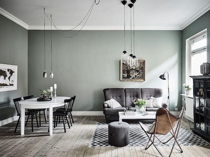 murs peinture vert de gris céladon dans un salon salle à manger scandinave, parquet en bois clair, suspensions originales, canapé et tabouret gris, tapis chevron noir et blanc, chaise en cuir, table blanche et chaises noires