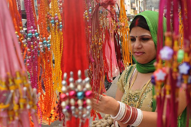 A shopper thumbs through selections of rakhi (sacred thread) in a store located in Amritsar, India, one day before the Raksha Bandhan festival on August 1, 2012. Raksha Bandhan is the Hindu celebration of brotherhood, siblings, and cousins where sisters tie rakhi on their brother's wrists for their protection.