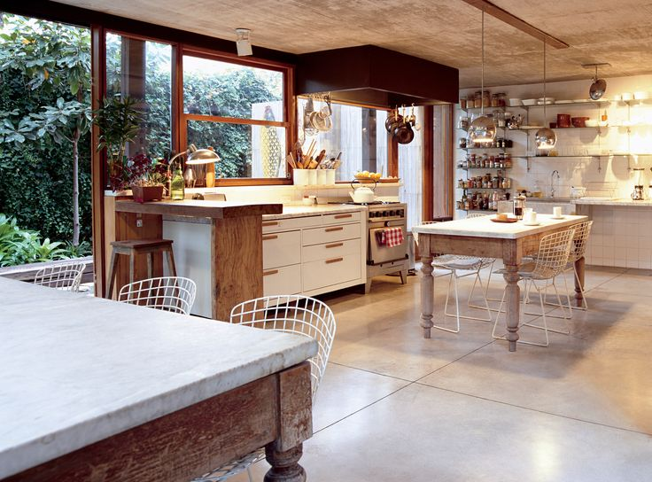 "In the kitchen, buffed concrete floors, chrome globe lights, and a fleet of Bertoia chairs comprise a sleek backdrop for quirkier pieces like the marble-topped wooden tables from a Catholic school, snagged at a local flea market. The secret to the spare, uncluttered shelves? A dispensa, or walk-in pantry, down the hall. ""We hide everything we don't want to see,"" Sticotti explains. ""We don't want to have to look at brands."""