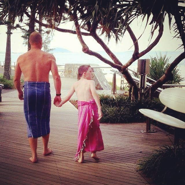 Dad and son walking along the boardwalk at Mooloolaba.  Family of Inspired 2 Give. Follow us on instagram!
