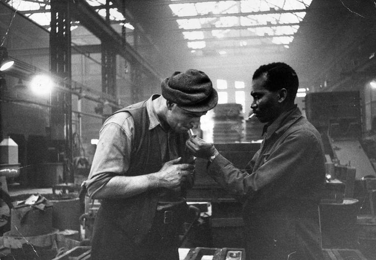 Jamaican immigrant Kwessi Blankson gives a light to workmate Jack White at The Phosphor Bronze Company in Birmingham. Published in Picture Post, January 1955.