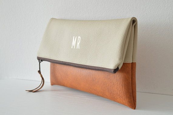 This monogrammed clutch is made of colorblock, high quality vegan (faux) leather.  Closes with a zipper. The interior is fully lined.  The letters