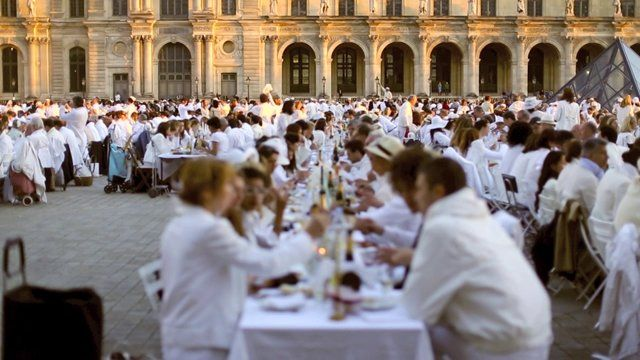 Diner en Blanc, also known as Diner in White, a top secret invitiation-only flash mob in Paris, France where 11,000 people dressed entirely in white clothes spontaneously set up tables and chairs in front of historic landmarks one night a year. This year's locations included the Eiffel Tower and the Louvre. Filmed by Stacy Reeves for L'Amour de Paris.