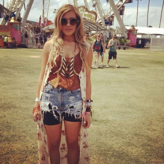 Lucy poses in front of the iconic Coachella ferris wheel in a Free People suede top, thrifted dress worn open as a vest, thrifted and DIY-frayed cutoffs, bike shorts, a DIY navajo harness, and Urban Outfitters sunnies.
