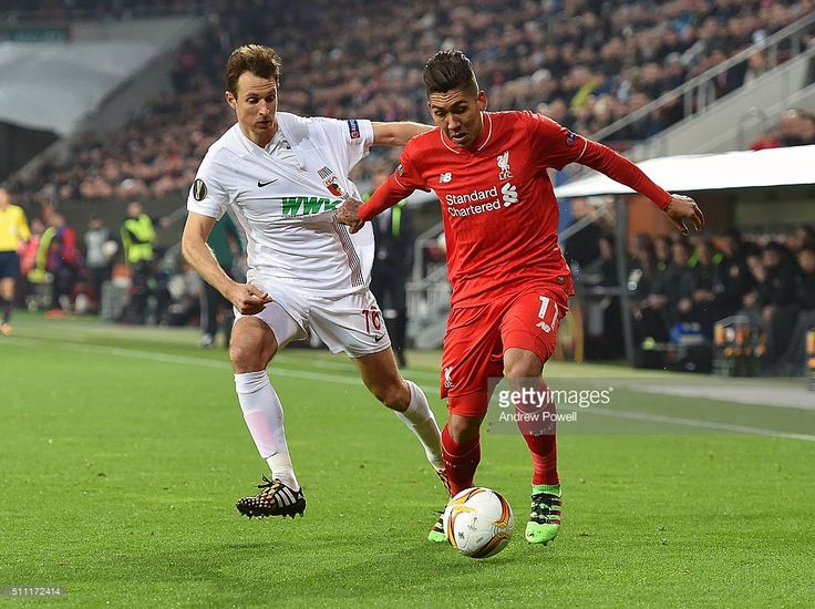 Roberto Firmino of Liverpool competes with Christoph Janker of Augsburg during the UEFA Europa League Round of 32: First Leg match between FC Augsburg and Liverpool on February 18, 2016 in Augsburg, Germany.
