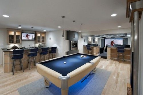 Well designed modern open floor plan basement,  blond wood with navy and stainless accents, pool table/ bar/ media room.