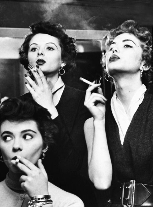 Smoking models learning proper cigarette smoking technique in practice for TV ad. 1953 Photo by Peter Stackpole.