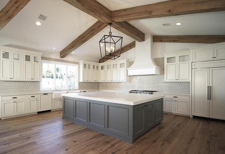 Lovely kitchen features a Darlana Large Lantern hanging over a gray kitchen island topped with light gray quartz countertop atop rustic wood floors.