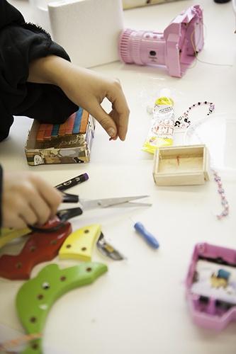 """Aan het werk tijdens het project """"duurzaam design, weggooien is zonde. Tijdens dit project maakten de leerlingen opberg-objecten van oude voorwerpen, verpakkingen, tijdschriften en oud speelgoed. Het project werd afgesloten met een heuse expositie tijdens de DDW2012."""