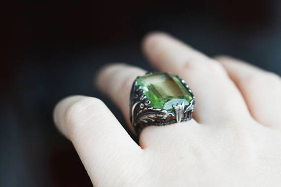 This is a boho style Art Nouveau olivine look-alike sterling silver berries and feathers setting ring. Might be from the 1900-1910s, or later. Signed for sterling. Used condition with some patina and wearmarks mostly on the stone (that I think is glass or other man made). Mixes well with