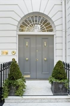 Gold and Grey front porch and entry. Grey double front doors with large arched window above.