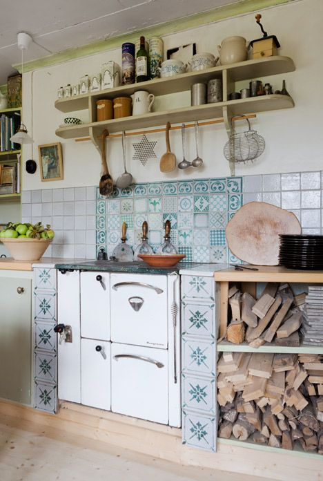 特にキッチンタイルの模様がカワイイ。カッティングボードが木の形そのままを活かしていたり、棚の上に並んだアンティークっぽい道具や薪がカントリーな雰囲気まんまん。