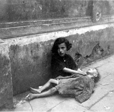 Warsaw, Poland, Starving children sitting on the pavement in the ghetto. Heinz Joest.