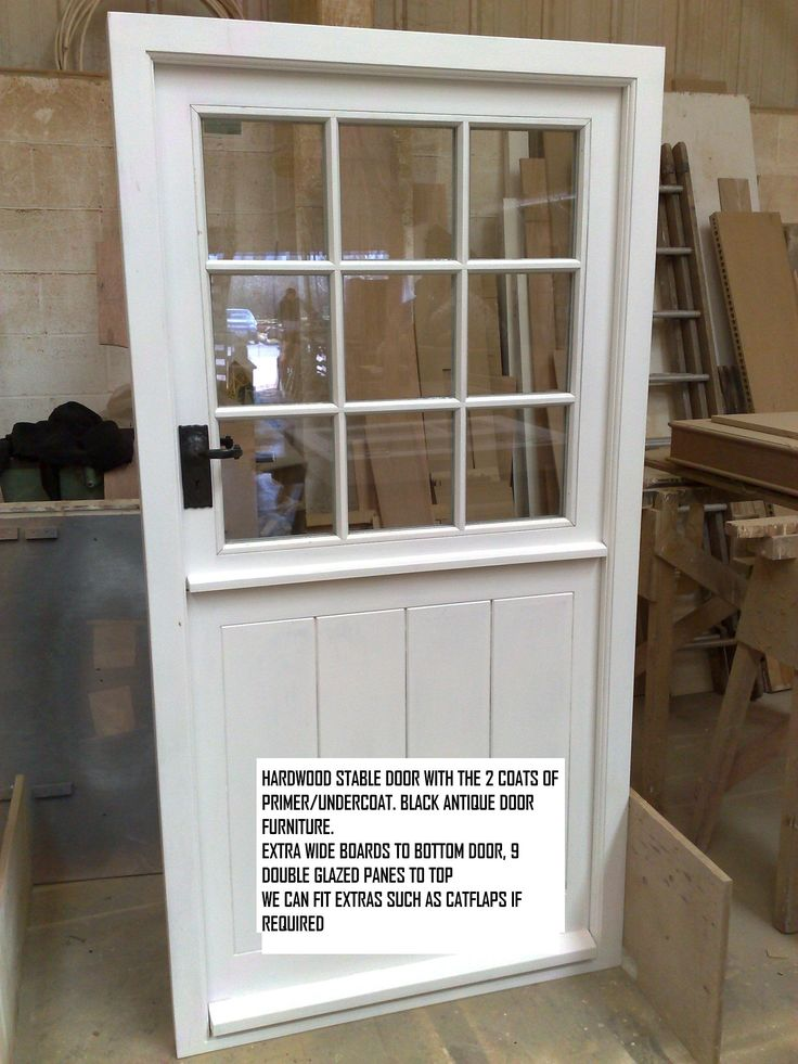 White painted traditional house stable door with wide boards and black antique door furniture. By Devon Custom Joinery