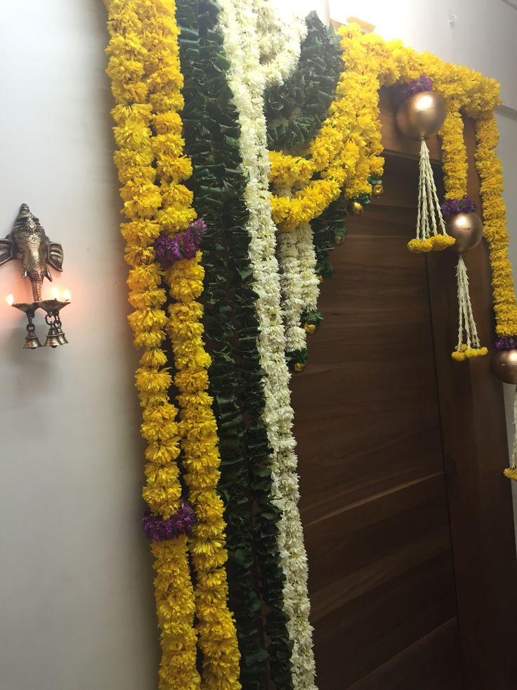 Door decor for Diwali with flower garlands and a Ganesh diya