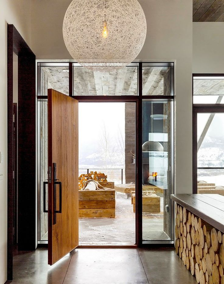 La porte d'entrée en bois massif et le sol en béton coulé de cette maison rustique