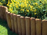 Wood edging is an easy to install option if soil needs to be retained from spilling into the yard. Conceal with plants so it will blend in, and apply wood preservative to prevent rotting.