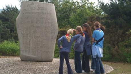 Guides looking at Brownsea Island scout stone © Vikki-Gridley-Haack
