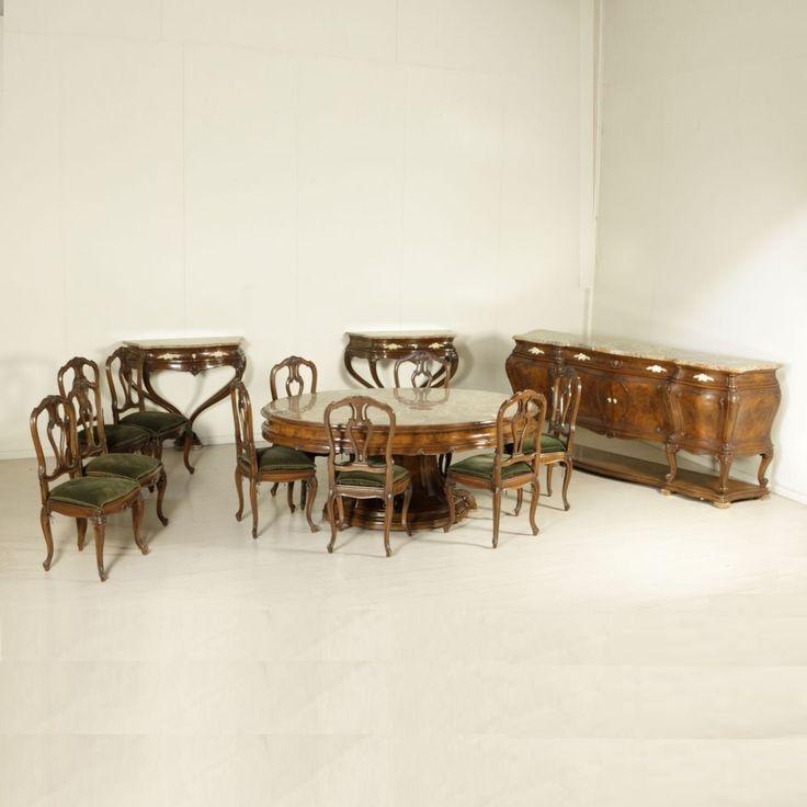 Arredo dalla linea mossa finemente intagliato con riserve in radica di noce. Composto da grande credenza con marmo crepato nel centro, grande tavolo con piano in marmo, coppia di eleganti consolle e gruppo di dieci sedie.