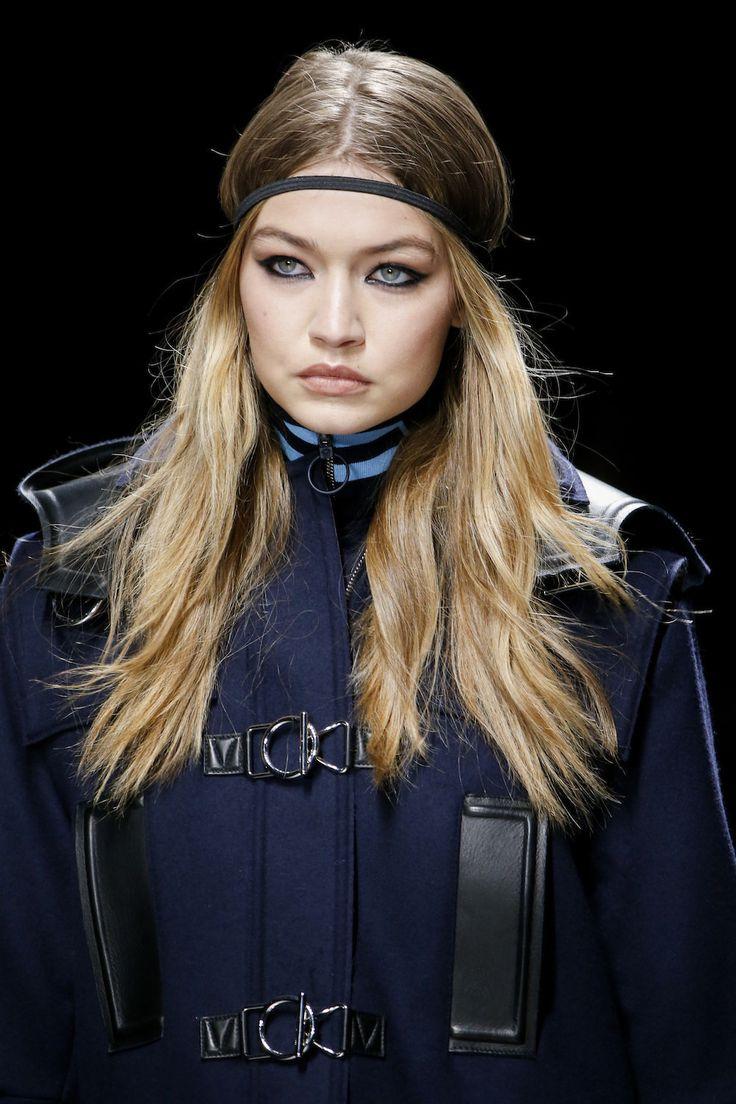 Donkerblauwe winged eyeliner, dik aangebracht rondom het hele oog en een lichte perzikkleur op de lippen bij Versace - De 10 meest opvallende beautylooks recht van de catwalk in Parijs en Milaan