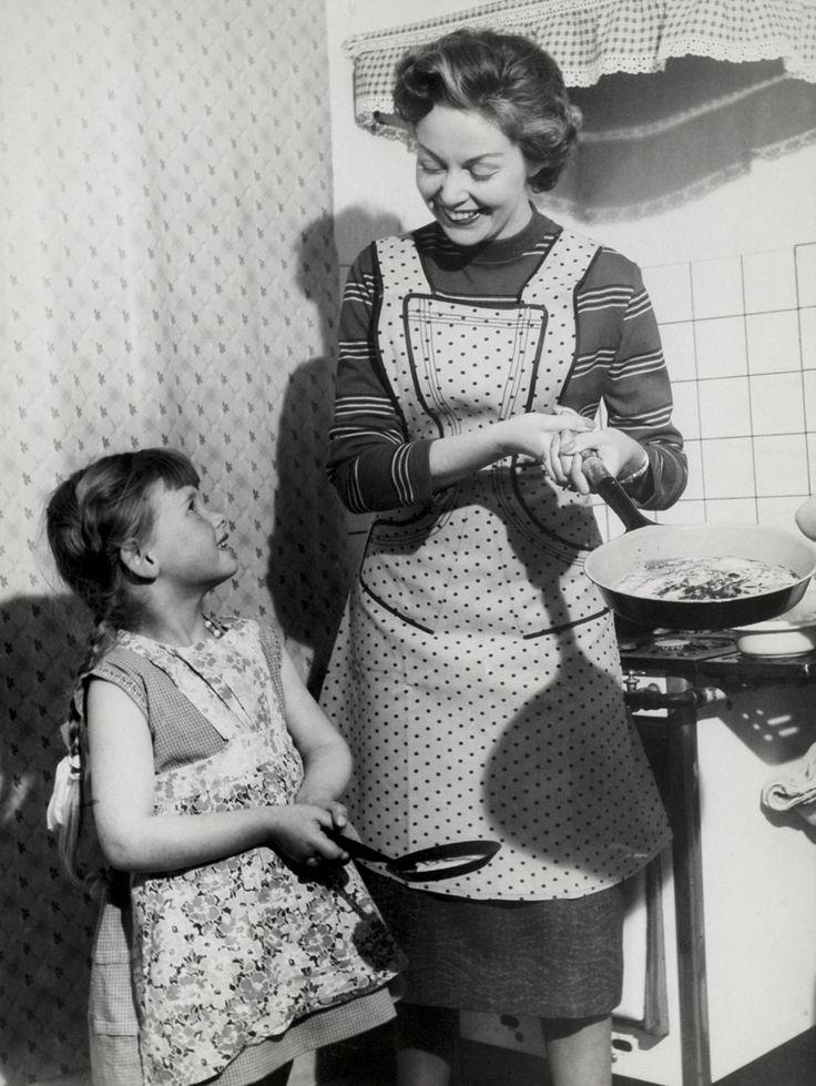 Een moeder met schort aan houdt een koekenpan met voedsel erin vast. Haar dochtertje staat ernaast, ook met schortje aan, en met een kleine koekenpan.