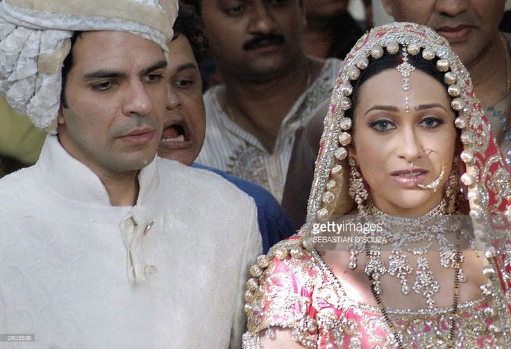 Indian film actress Karishma Kapoor (R) and her new husband Sanjay Kapoor (L) stand for a photo call in Bombay,29 September 2003, following the couples wedding ceremony at the Kapoor's ancestral home. The wedding of Indian actress Karishma Kapoor to her childhood friend Sanjay Kapoor was attended by a large number of filmstars and celebrities. AFP PHOTO/Sebastian D